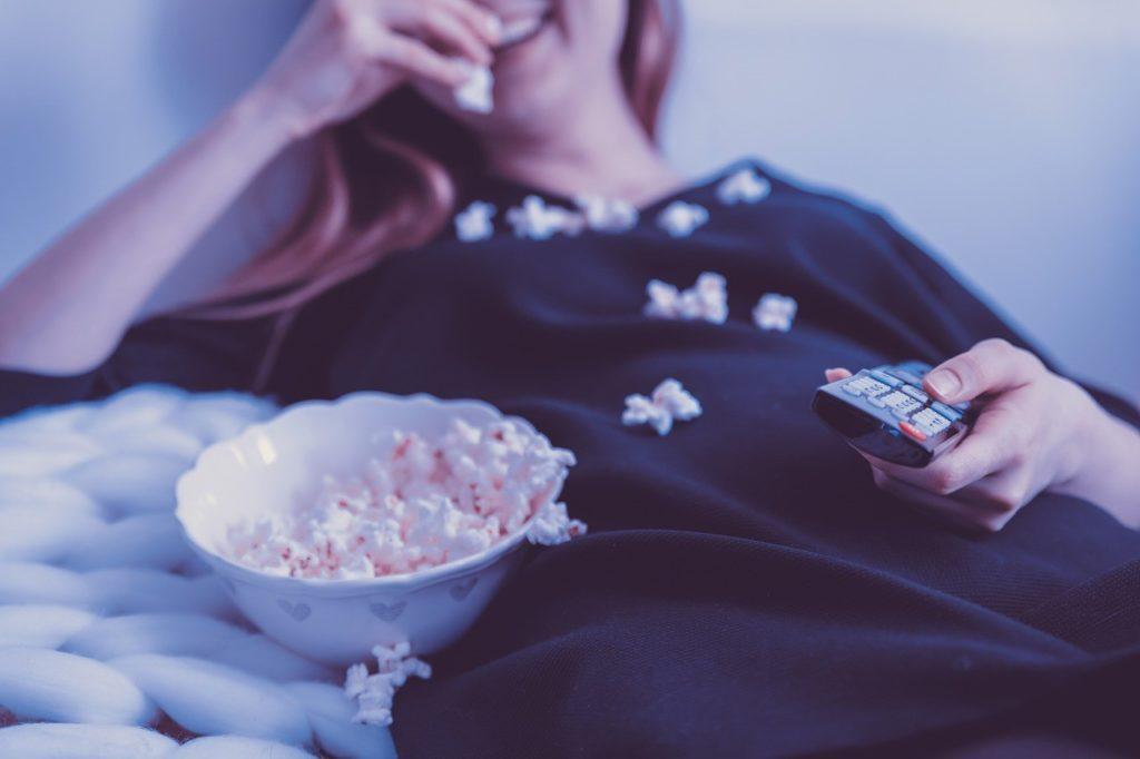 fille en train de regarder la télé avec du popcorn